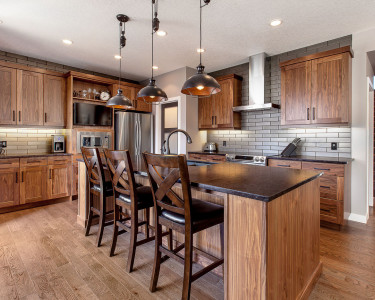 Contemporary Black Walnut kitchen in a natural stain, shaker door, custom wine rack, built-in microwave and trim kit, stainless steel hood fan, dark granite countertops, subway tile backsplash, available at Superior Cabinets.