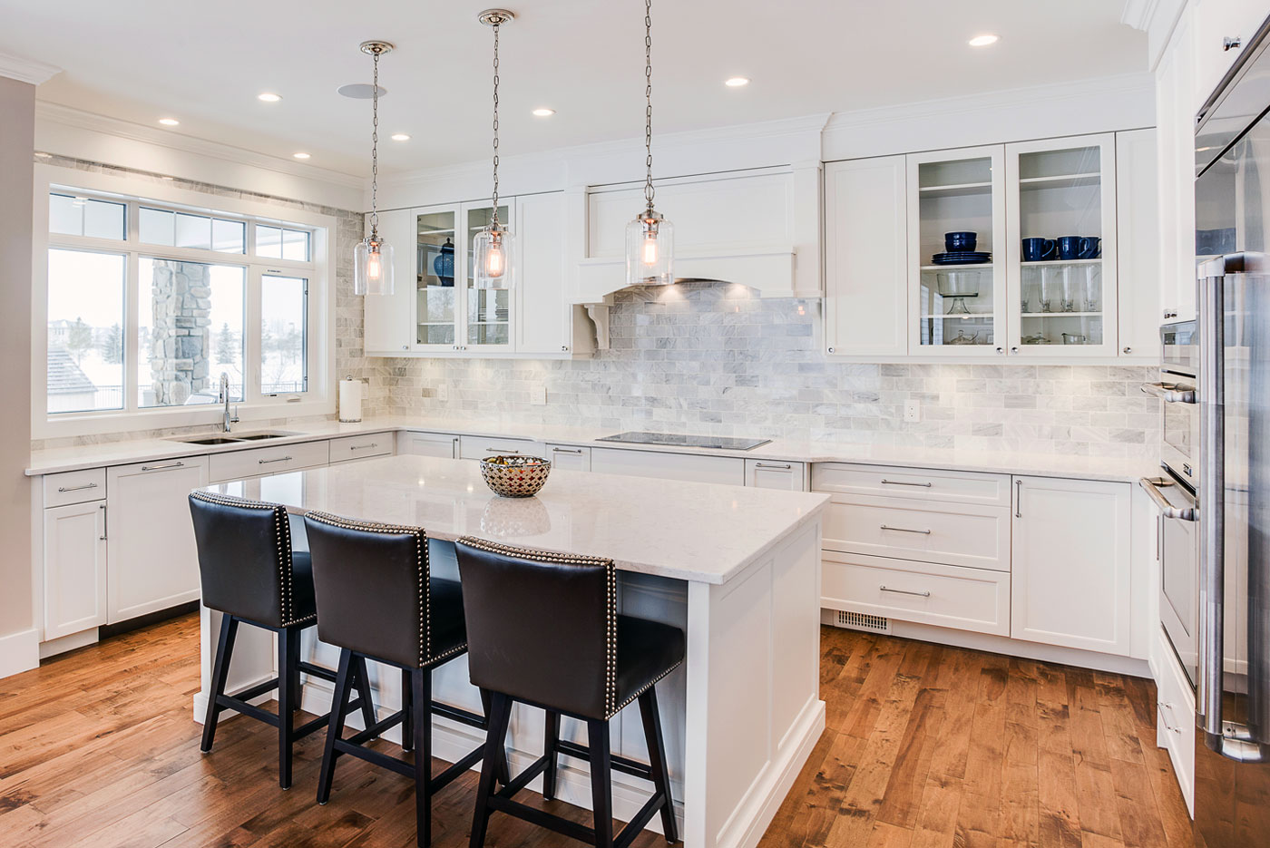 Enormous open concept traditional kitchen with white painted maple cabinets, quartz countertops and a Carrera marble tiled backsplash, available at Superior Cabinets.
