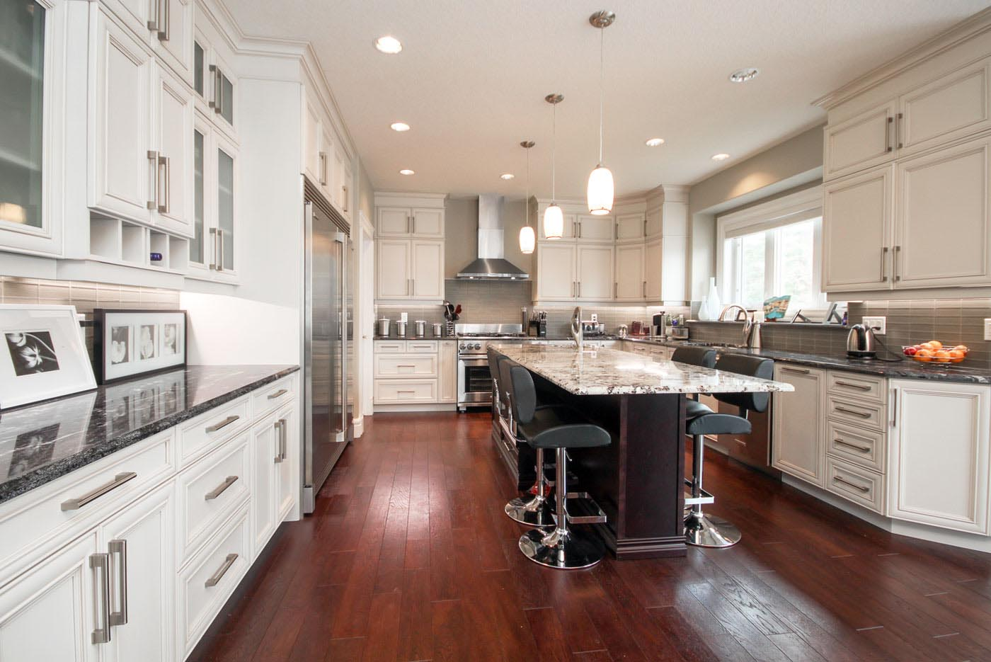 Contemporary two toned kitchen featuring painted white maple and dark French roast stained cabinetry on maple, granite countertops, auburn hardwood floor, stacked uppers, stainless steel hood fan, available at Superior Cabinets.