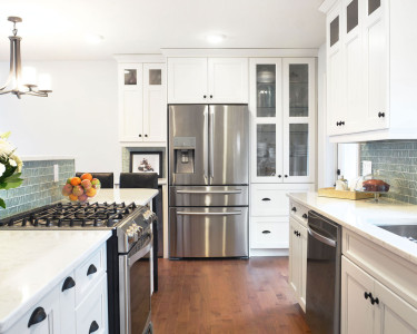 Breathtaking contemporary kitchen with painted white maple cabinets, white quartz countertops and a warm maple hardwood floor, available at Superior Cabinets.