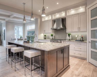 Contemporary two-toned kitchen with painted white maple cabinets on the perimeter and medium stained maple cabinets on the island, available at Superior Cabinets.
