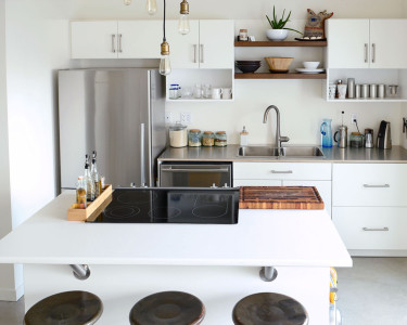 Eclectic kitchen featuring painted white MDF cabinets/cabinetry/cupboards, floating wood shelves, built-in cooktop, vintage bar stools, available at Superior Cabinets.