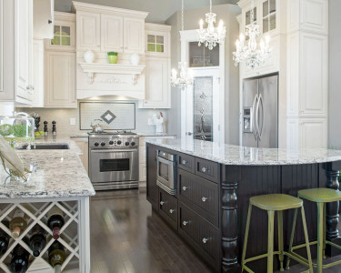Traditional style kitchen featuring with two-toned cabinetry, perimeter in a painted white maple and the island in a dark stained maple, wine rack, quartz countertops, dark hardwood floor, custom wood hood, tiled backslash, available at Superior Cabinets.