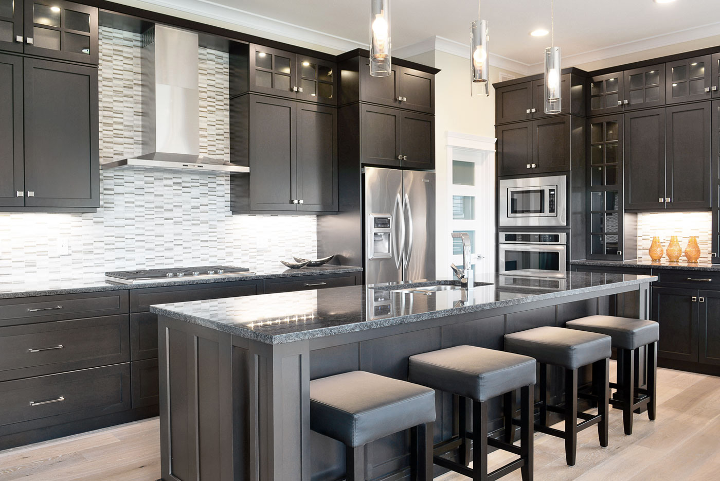 Dark Maple cabinetry in an open concept contemporary styled kitchen from the STARS Home Lottery Saskatchewan Show Home. Cabinetry designed and provided by Superior Cabinets.