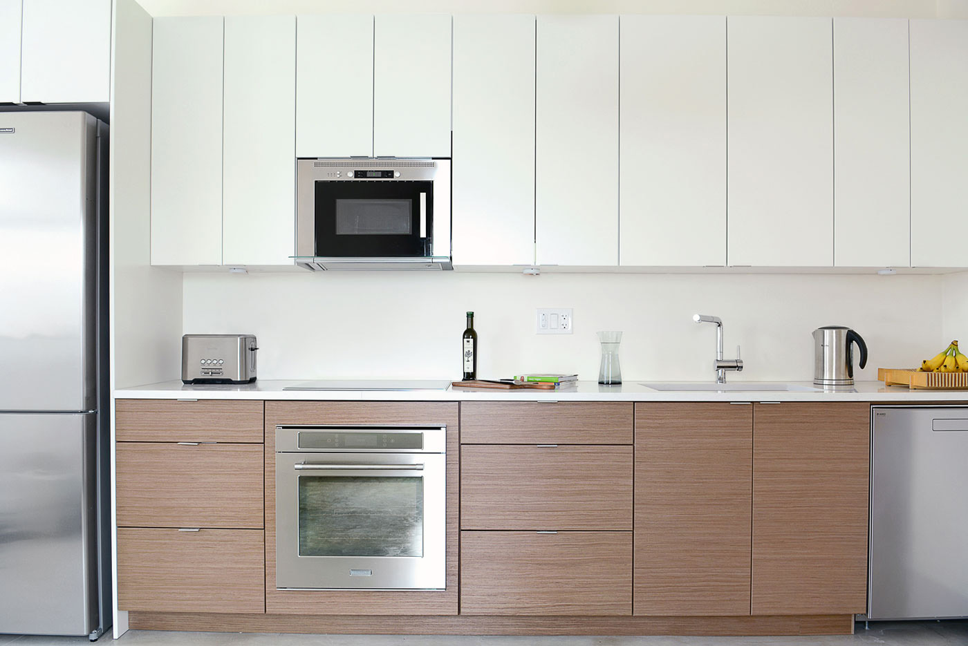 Ultra-Modern two-toned kitchen featuring smooth white painted MDF upper cabinets and a warm exotic walnut with urban horizontal wood grain, available at Superior Cabinets.