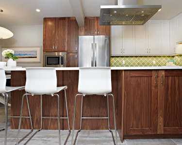 Eclectic two-toned kitchen featuring painted white maple cabinets with natural black walnut accents, stainless steel canopy hood fan, built-in microwave, tile foot, green lantern Mediterranean backslash, available at Superior Cabinets.