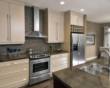 Contemporary kitchen in a MDF Painted - Smooth Cobblestone finish, stainless steel canopy hood fan, stainless steel appliances, slide in gas range, cubby hole wine rack above fridge, available at Superior Cabinets Saskatoon, Regina, Calgary, Edmonton.