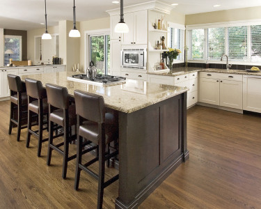 Contemporary two-toned kitchen with light cabinets on the perimeter and a large island in a dark stain on maple, built-in gas cooktop, granite countertops, panel ready dishwasher, available at Superior Cabinets Saskatoon, Regina, Calgary, Edmonton.