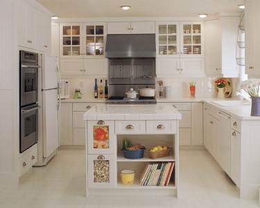 Traditional country styled kitchen in a smooth painted white mdf finish, stainless steel gas range, built-in double wall ovens, island with cookbook storage, glass upper doors with mullion inserts, available at Superior Cabinets Saskatoon, Regina, Calgary, Edmonton.