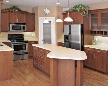 Contemporary kitchen with medium stained cabinets cupboards, stainless steel appliances, large angled island, light colored countertops, available at Superior Cabinets Saskatoon, Regina, Calgary, Edmonton.