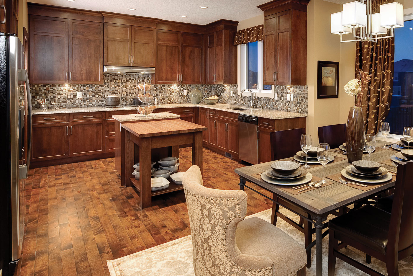 Contemporary kitchen with medium stained cabinets cupboards, stainless steel appliances, large island with butcher block top, light colored granite countertops, available at Superior Cabinets Saskatoon, Regina, Calgary, Edmonton.