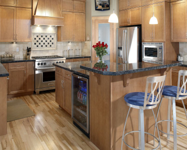Contemporary kitchen with medium stained cabinets cupboards, stainless steel appliances, wolf gas range, large island with raised eating bar, dark granite countertops, available at Superior Cabinets Saskatoon, Regina, Calgary, Edmonton.