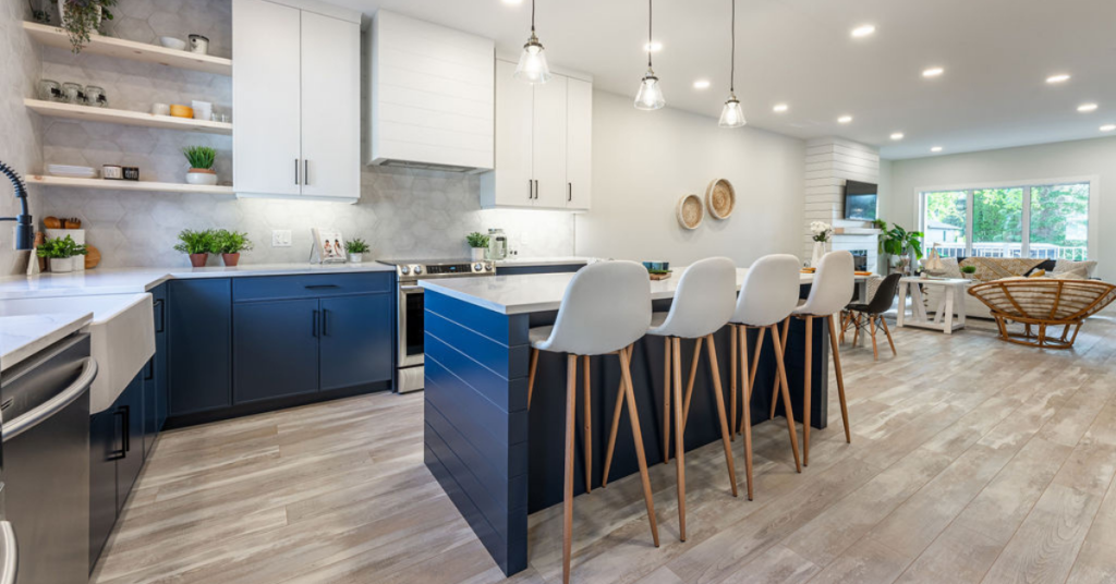 A modern farmhouse kitchen with dark blue lowers and island and white upper cabinets.