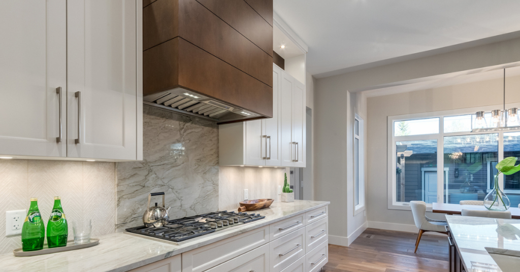 A kitchen with a custom square and sleek modern decorative wood hood fan by Superior Cabinets.